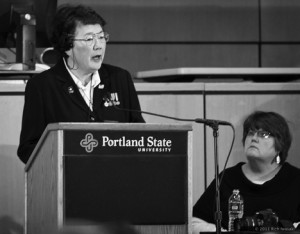 Oregon Nisei Veterans Commander Setsy Larouche speaks at the 2011 Day of Remembrance event, Hoffmann Hall, Portland State University, Portland, Oregon. Marty Davis (right), editor of Just Out magazine, spoke as part of the panel.